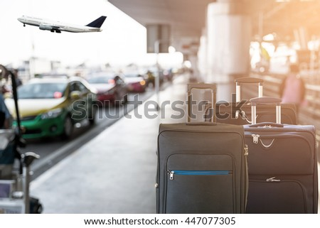 Closeup of group of luggage with the blurred of the taxi park at the airport terminal background.