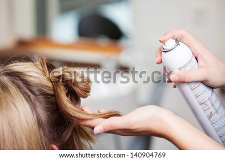 Closeup of hairdresser's hands using hairspray on client's hair at salon