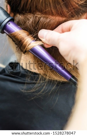 Closeup of hairdresser's hands with curling iron are making hairdo at hair salon background. Hairstyle concept.