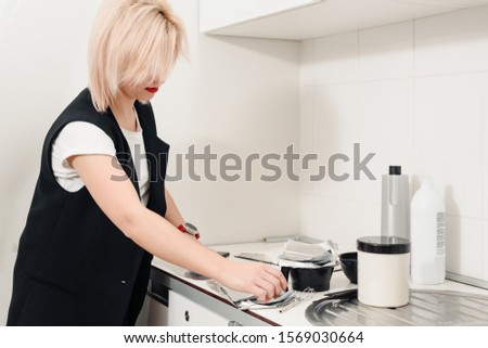 Closeup of hairdresser weighing proportion of hair dye on electronic scales