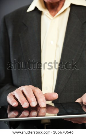 Closeup of hand from senior man in dark suit against grey wall. Using tablet. Well dressed. Studio shot.
