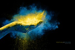 Closeup of hand holding colorful holi powder surrounded by a vibrant color explosion with falling powder over a black background with copy space. Festival of colors