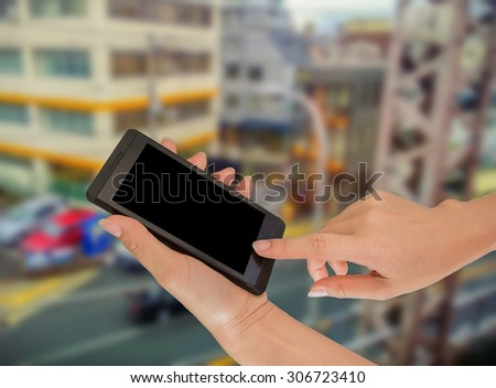 Closeup of hand holding phone in city #306723410
