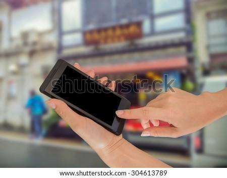 Closeup of hand holding smart phone on street #304613789