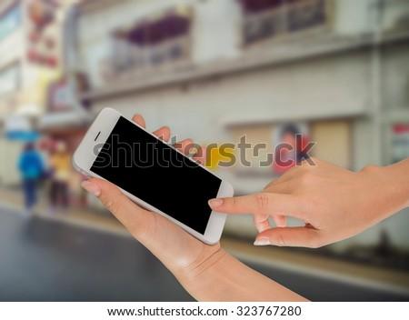 Closeup of hand holding smart phone on street #323767280