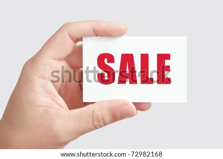 """Closeup of hand holding white advertising card with word """"SALE"""" written in red, isolated on gray background"""
