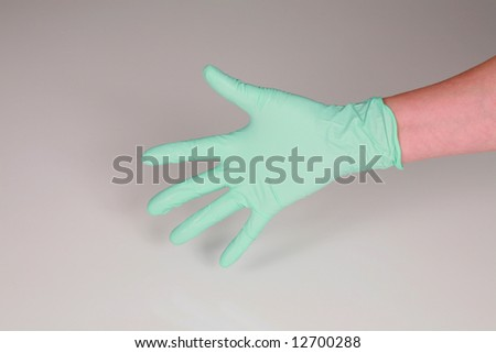 closeup of hand in green medical glove