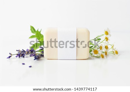 Closeup of hand made herbal soap bar in blank paper label package. Mint leaves, lavender and feverfew flowers on white table backround. Spa concept. Skin product mockup scene. Cosmetic product. #1439774117
