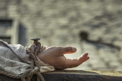 Closeup of hand nailed on wooden cross. Crucifixion of Jesus Christ.