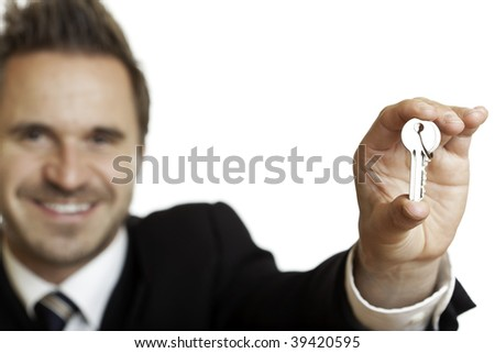 Closeup of hand of businessman overgiving a key. Isolated on white, focus on key.