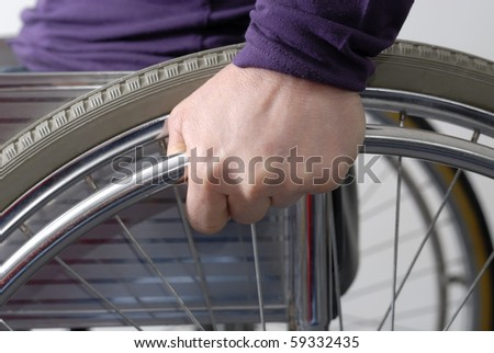 ClosEup of hand of disabled person on the wheel of a wheelchair - stock photo