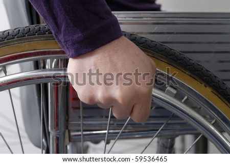 Closeup of hand of disabled person on the wheel of a wheelchair
