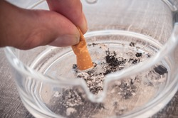 closeup of hand of man with cigarette and ashtray