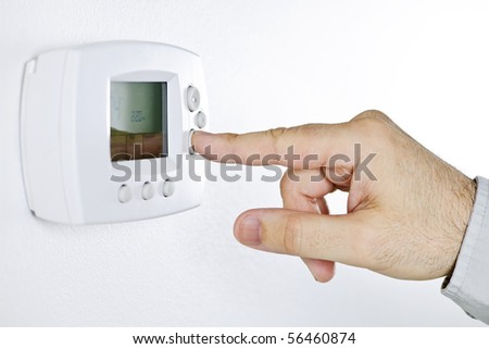 Closeup of hand pressing button on digital thermostat