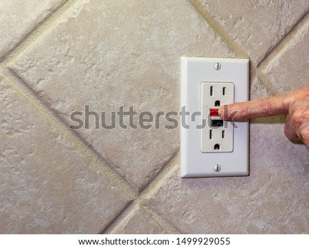 Closeup of hand resetting tripped GFI electricity receptacle. Residential ground fault interrupter electric socket plug and wall plate. #1499929055