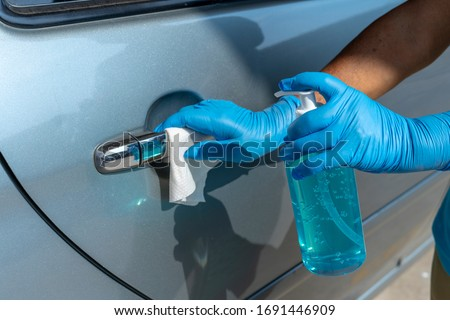 Closeup of hand spraying a blue sanitizer from a bottle for disinfecting door handle of a white car.Antiseptic,disinfection ,cleanliness and healthcare,Anti bacterial and Corona virus, COVID-19.