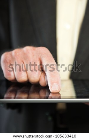 Closeup of hand using tablet from senior man in dark suit against grey wall. Well dressed. Studio shot.