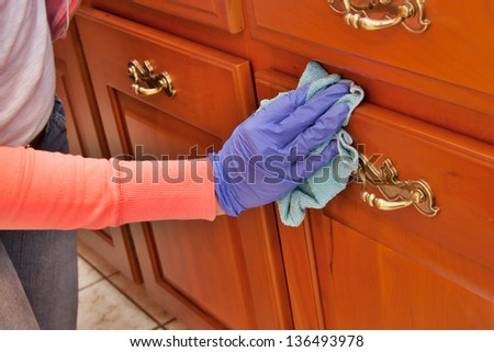 closeup of hand with purple latex glove cleaning  wooden cabinet with green microfiber cloth