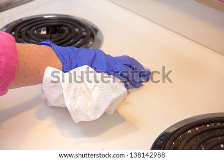 closeup of hand with purple latex gloves cleaning  stove with paper towels