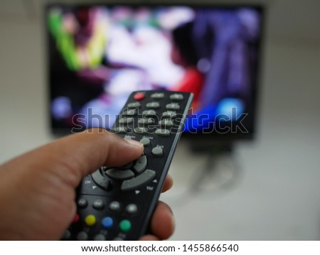 closeup of hand with the remote control television and presses the button. #1455866540