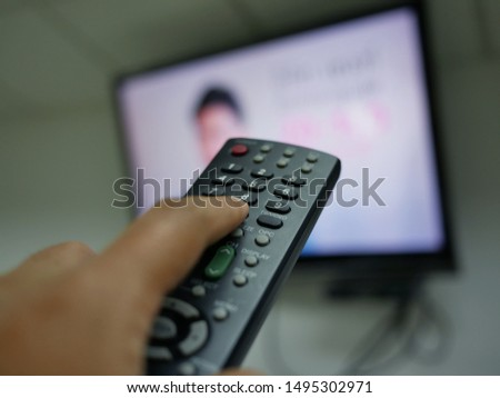 closeup of hand with the remote control television and presses the button. #1495302971