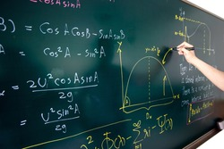 Closeup of hand writing complicated math equation on black board.