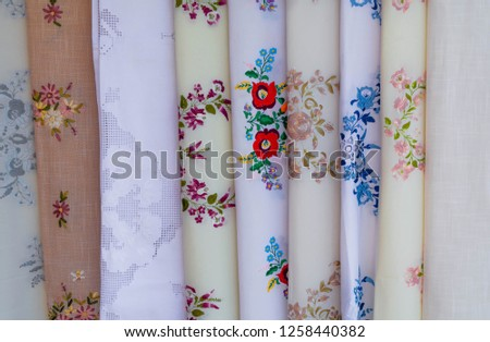 Closeup of handmade embroidered curtain from Hungary. Close up white,blue,red,brown and green vintage curtain with embroidered orange,red,blue and green flowers hanging.Hungarian traditional embroider