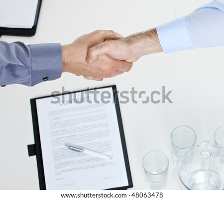 Closeup of hands, businessmen shaking hand over contract on meeting table in office.