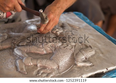 Closeup of hands carving silver. Process of silver carving, Chiang Mai, Thailand.