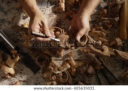 Closeup of hands carving wood.