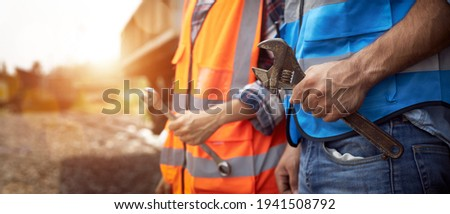 Closeup of Hands of maintenance worker holding a wrench while standing outdoors. The concept of off-site emergency service and assistance. Photo stock ©
