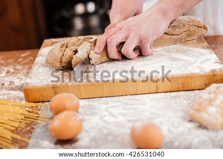 Closeup of hands of man baker cutting bread on wooden board on the kitchen - Shutterstock ID 426531040