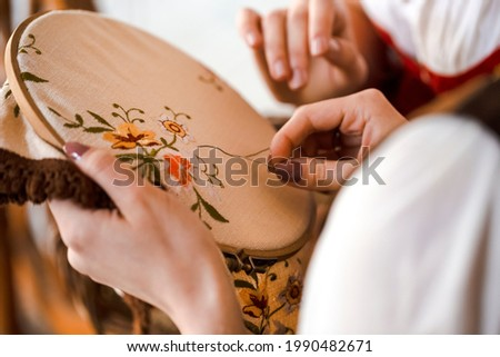 Closeup of Hands of Young Caucasian Woman Posing With Fancywork Hoop in Retro Dress In Rural Environment. Horizontal Image Stock photo ©