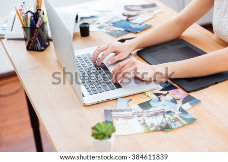 Closeup of hands of young woman photograper typing on laptop keyboard and using graphic tablet