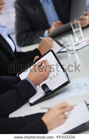 Closeup of hands on business meeting at office writing notes to personal organizer,