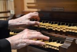 Closeup of hands playing an organ.