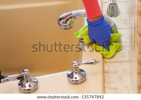 closeup of hands with purple latex gloves cleaning  bathroom with green microfiber cloth