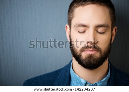 Closeup of handsome businessman with eyes closed against blue background
