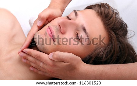 Closeup of Handsome man enjoying face massage in spa salon - stock photo