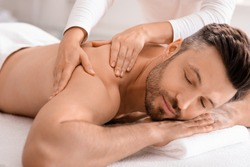 Closeup of handsome man having full body massage at male spa. Unrecognizable female therapist rubbing middle aged man shoulders, making relaxing massage. Spa, massage, cosmetology for men