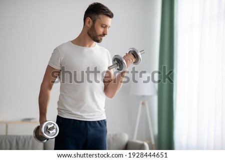 Closeup of handsome middle-aged man doing dumbbell workout at home, working on arms strength, looking at his biceps, copy space. Athletic man lifting dumbells up over living room interior