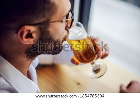 Closeup of handsome unshaven man in shirt sitting in pub next to window, drinking beer and relaxing after work.