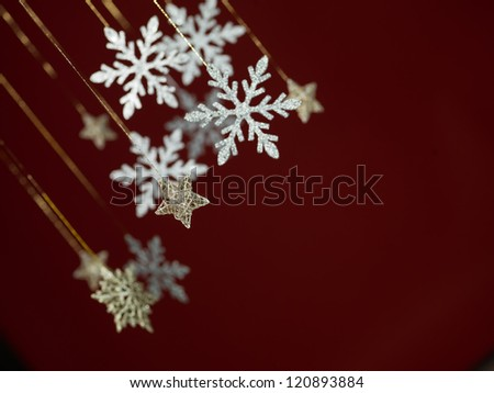 closeup of hanging christmas decorations in shape of silver snowflakes and stars with glitter on dark red background