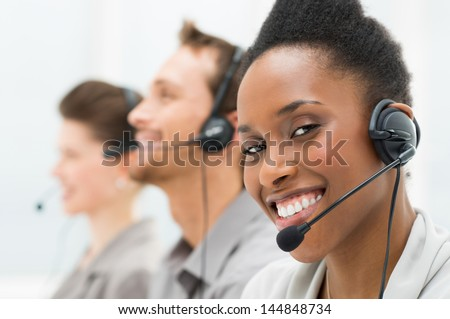 Closeup Of Happy African American Telephone Operator with Her Colleagues - stock photo
