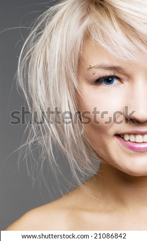 closeup of happy blond with blue eyes over grey background