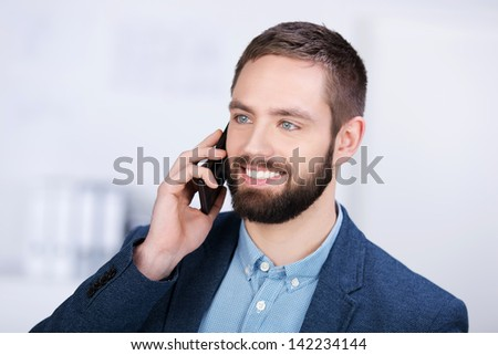 closeup of happy businessman using cell phone in office