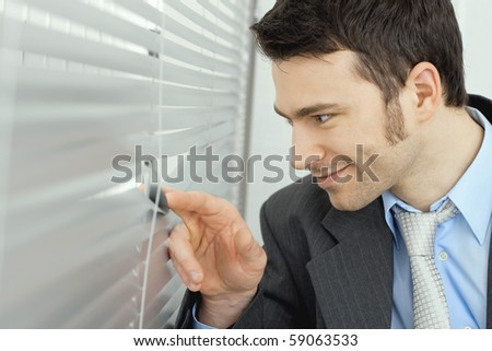 Closeup of happy curious businessman looking out the window through rolling shutter, smiling.