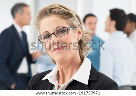 Closeup Of Happy Mature Businesswoman In Front Of Colleague