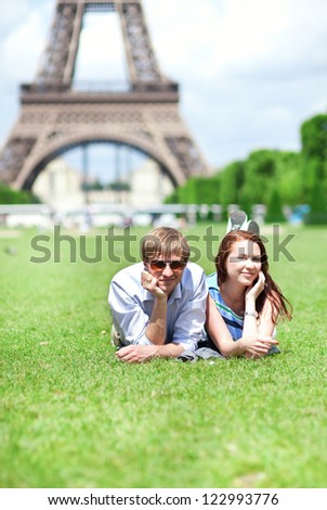 Closeup of happy positive couple laying on the grass near the Eiffel tower