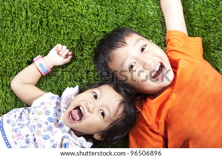 Closeup of happy young children lying on the green grass